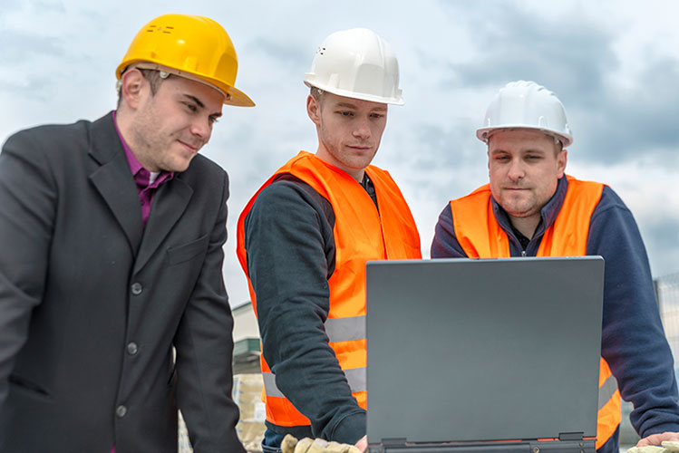 Three engineers discussing the plans in a laptop