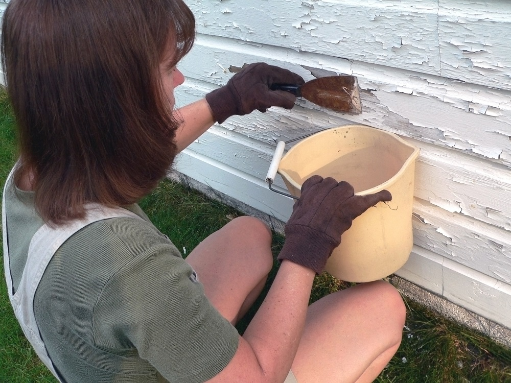 Woman scraping chipped paint off the side of a house