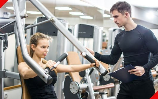 Sporty Girl Training On Exercise Machine With Support Of Her  Trainer In Gym