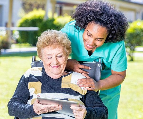 Nurse Explaining Tablet Use to Elder Woman