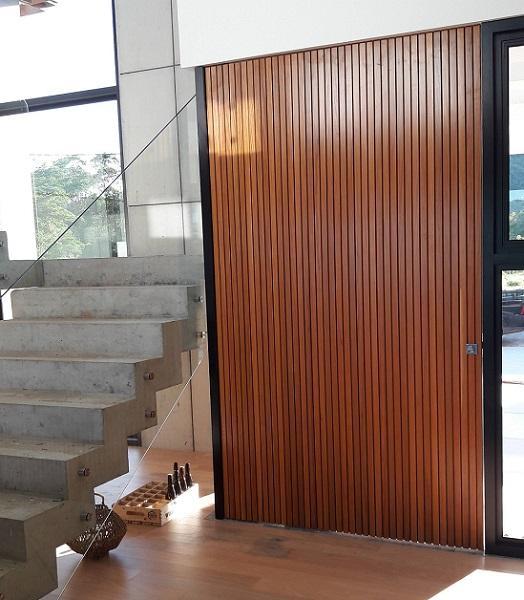 Porta 700 - Porta de madeira ripada e sistema de abertura pivotante.