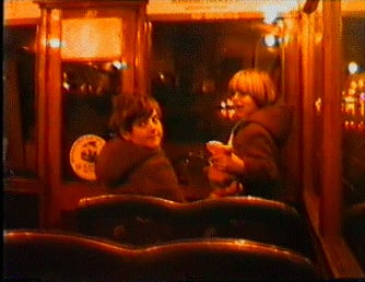 Susan Brownrigg (left), child with sister on tram during Blackpool Illuminations. Still captured taken from home movie.