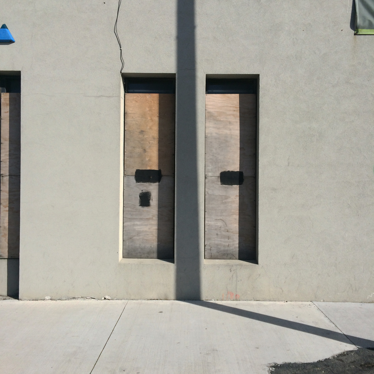 Boarded up windows on a warm grey building with a shadow from a light pole.