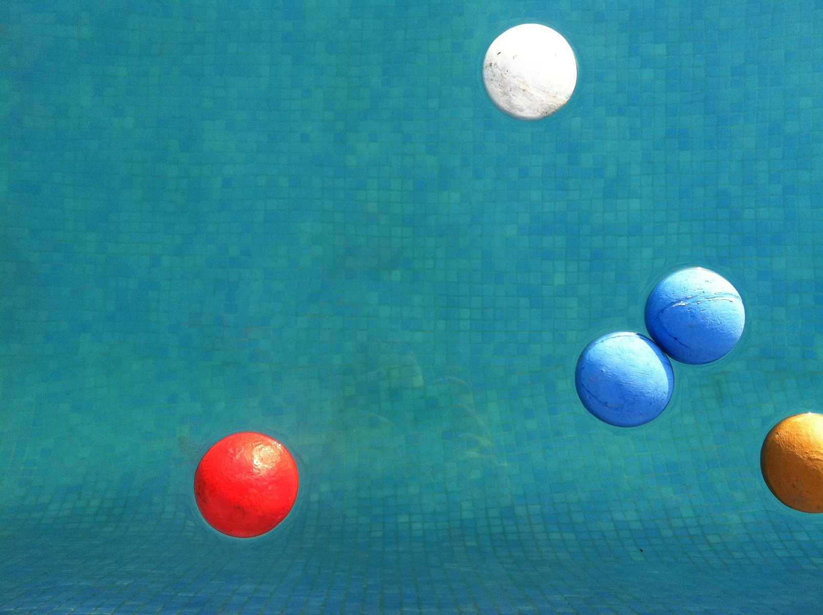Five painted balls, blue, red, yellow and white, float in a sunny, blue-tiled pool.