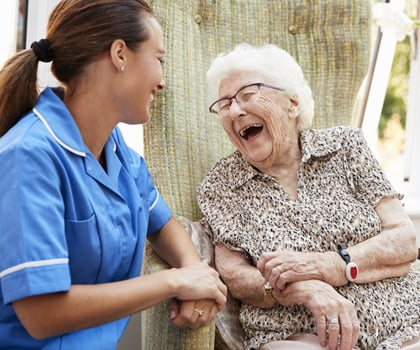Senior Woman Sitting In Chair And Laughing With Nurse