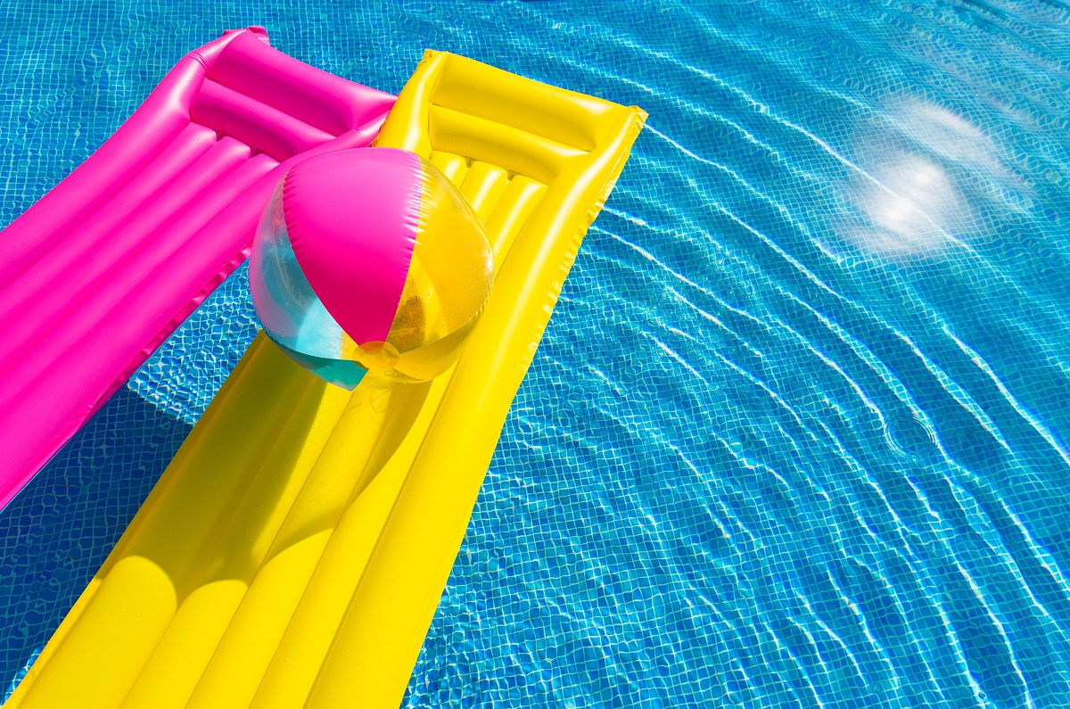 Two Yellow and Pink Floaties and Beach Ball in Pool