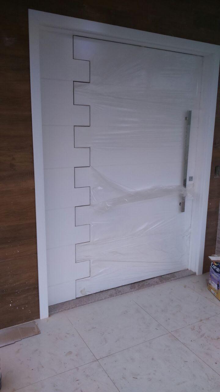 Porta 702 - Porta de madeira, sistema de abertura pivotante, frisos horizontais e pintada em laca branca.
