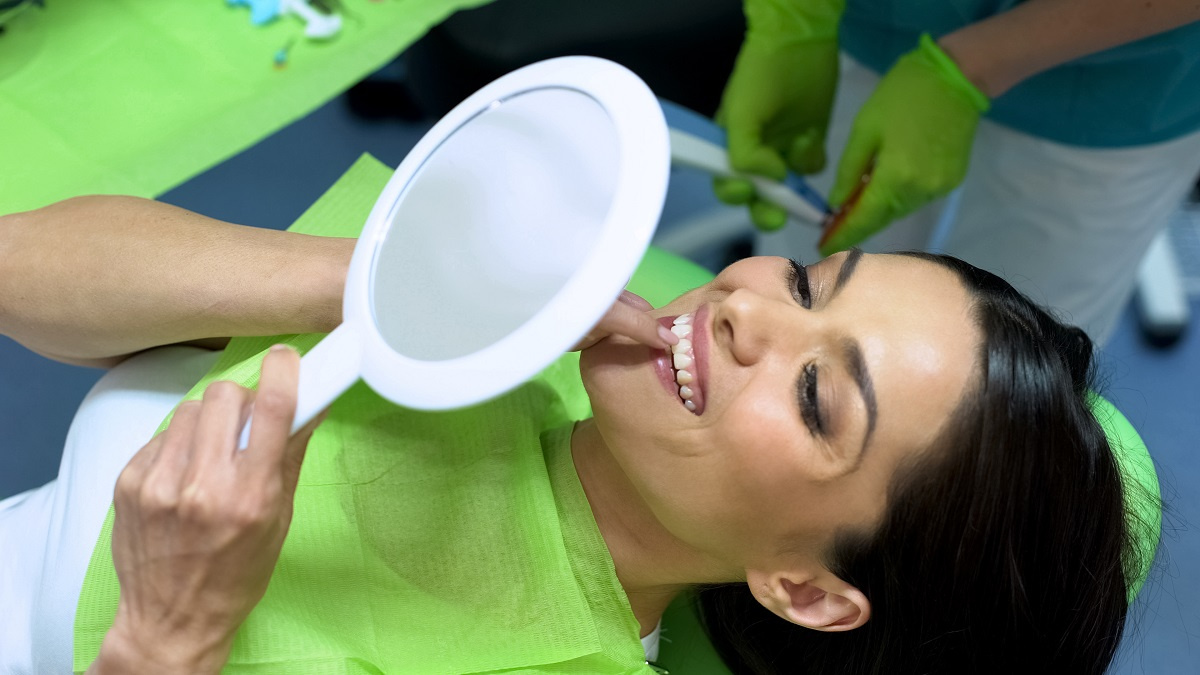 Woman in dentist chair examining teeth in mirror