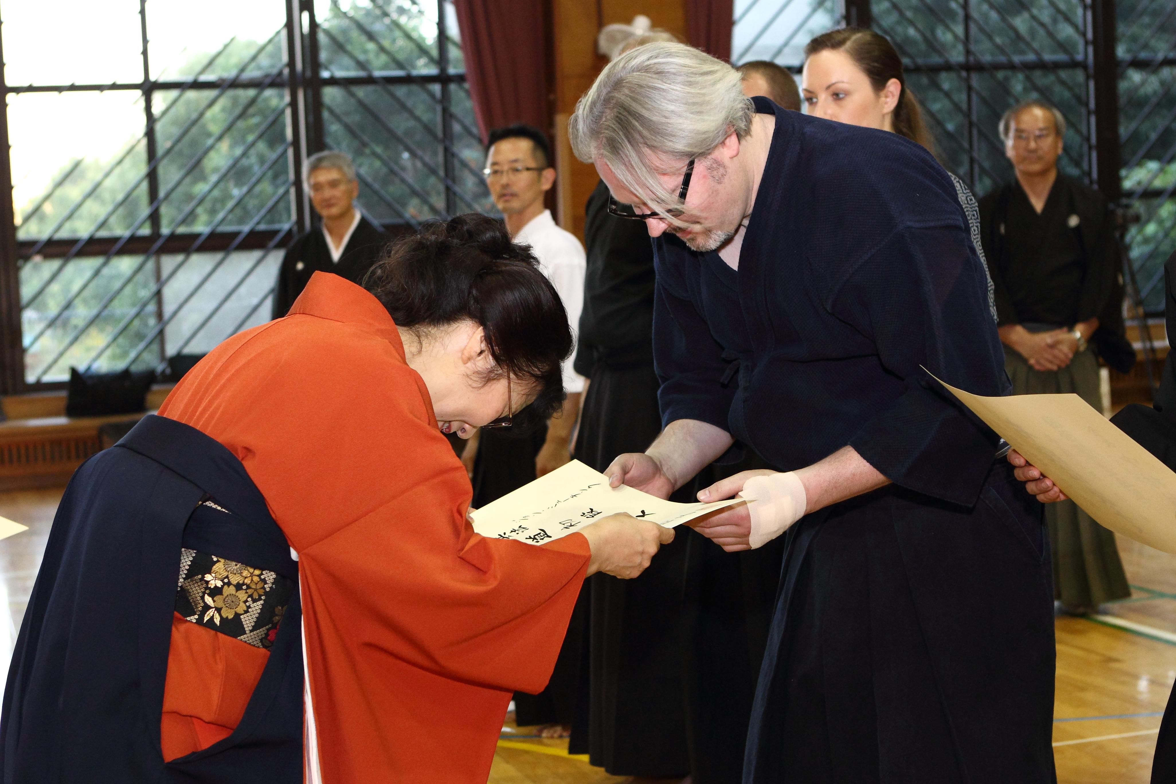Tex receiving Shodan from Nakamura Tomoko Kaichou.