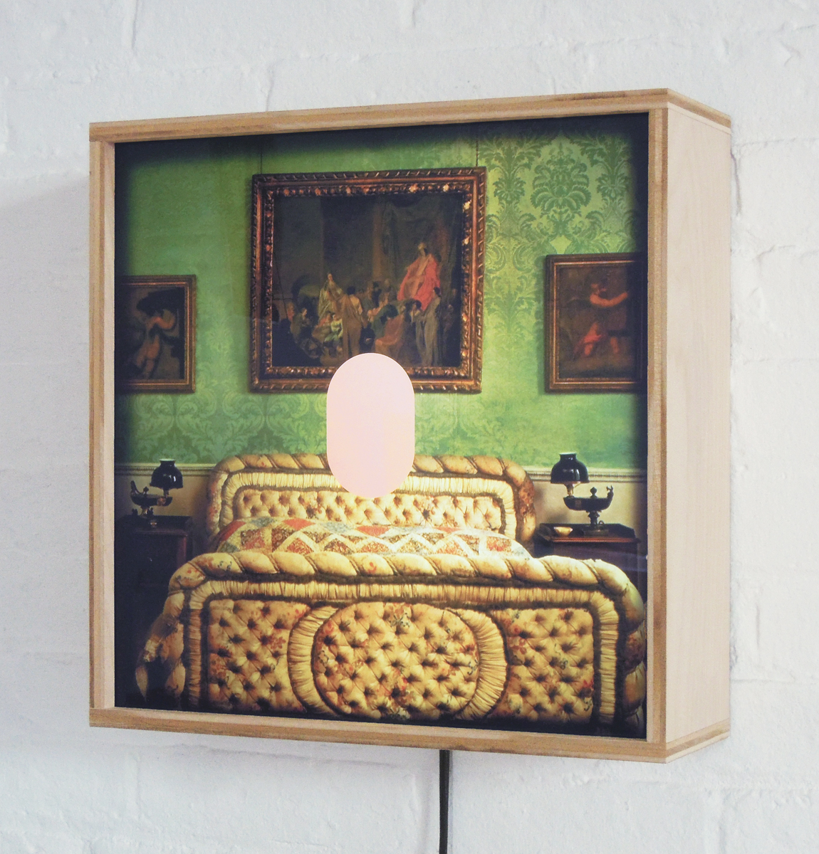 A plywood lightbox contains an image of an opulent bedroom and a pink oval.