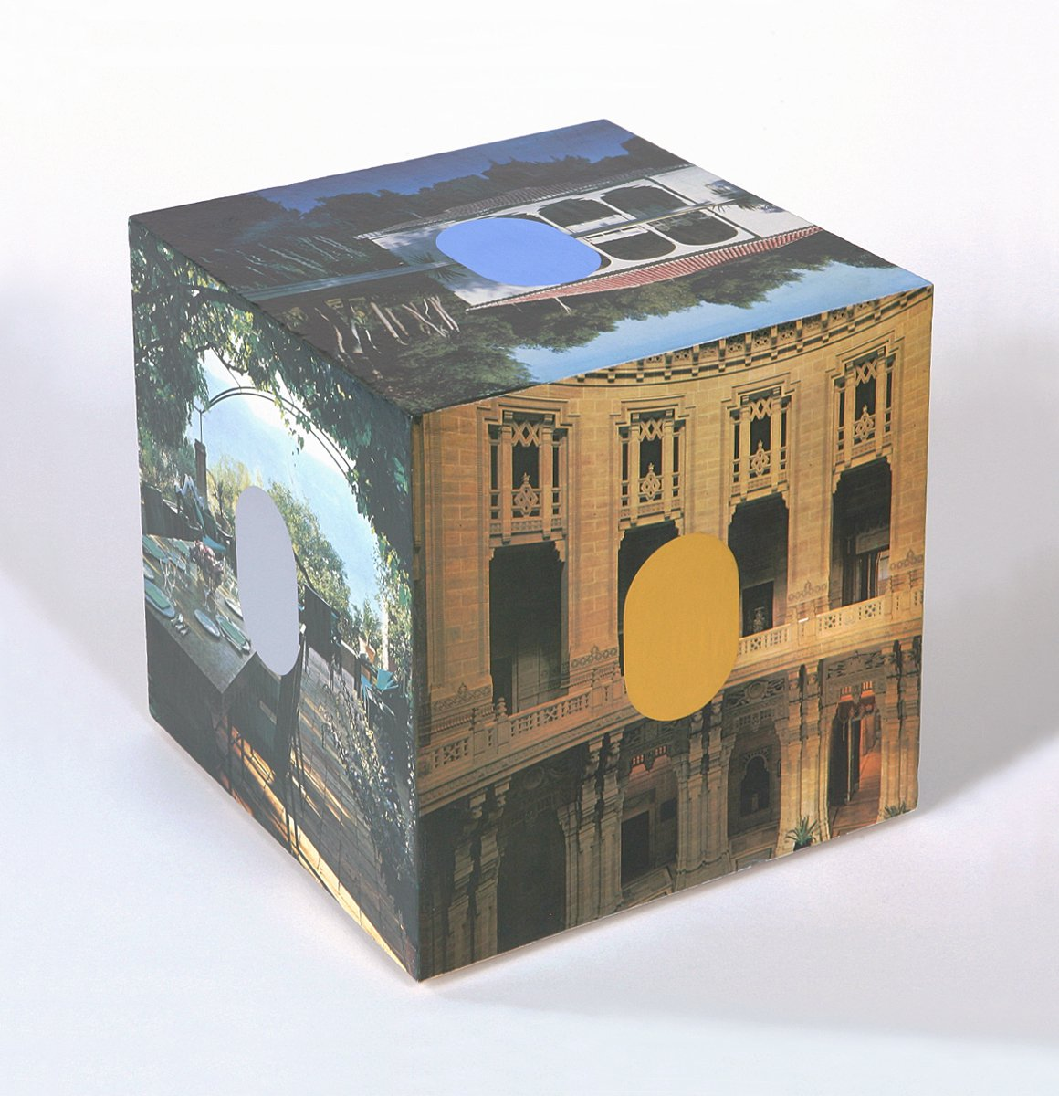A cube with architectural images and blue, grey and ochre ovals on the outside.
