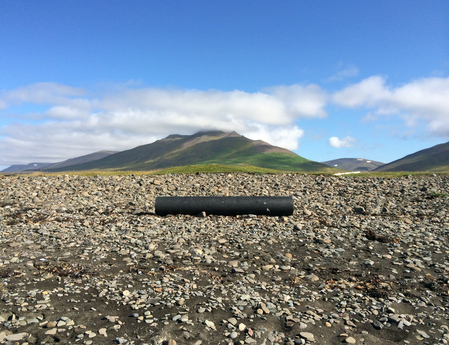 A black plastic tube on a gravel beach with mountains behind, and a sunny sky.