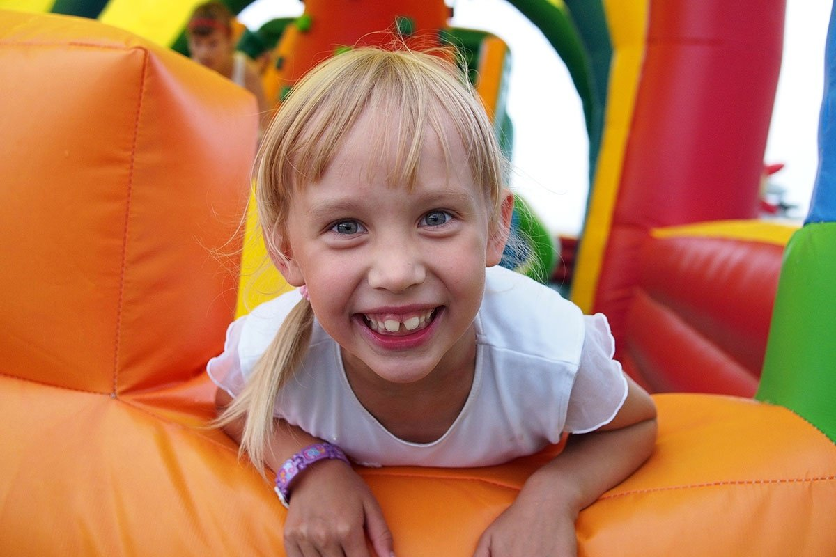 Child Playing In Bouncy Castle