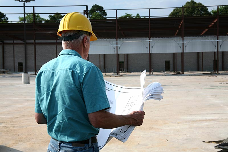 Builder studying the plans at a construction site