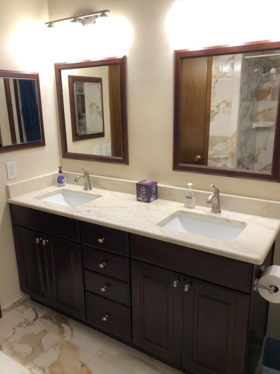 Bathroom vanity with double sinks featuring Dolomite countertop, beautifully framed matching mirrors, and medicine cabinet.