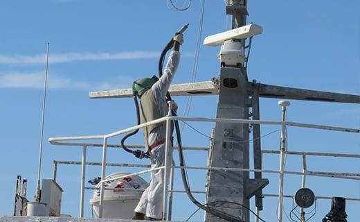 Sandblaster at Work on Ship