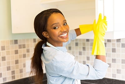 African Woman Cleaning Cupboard