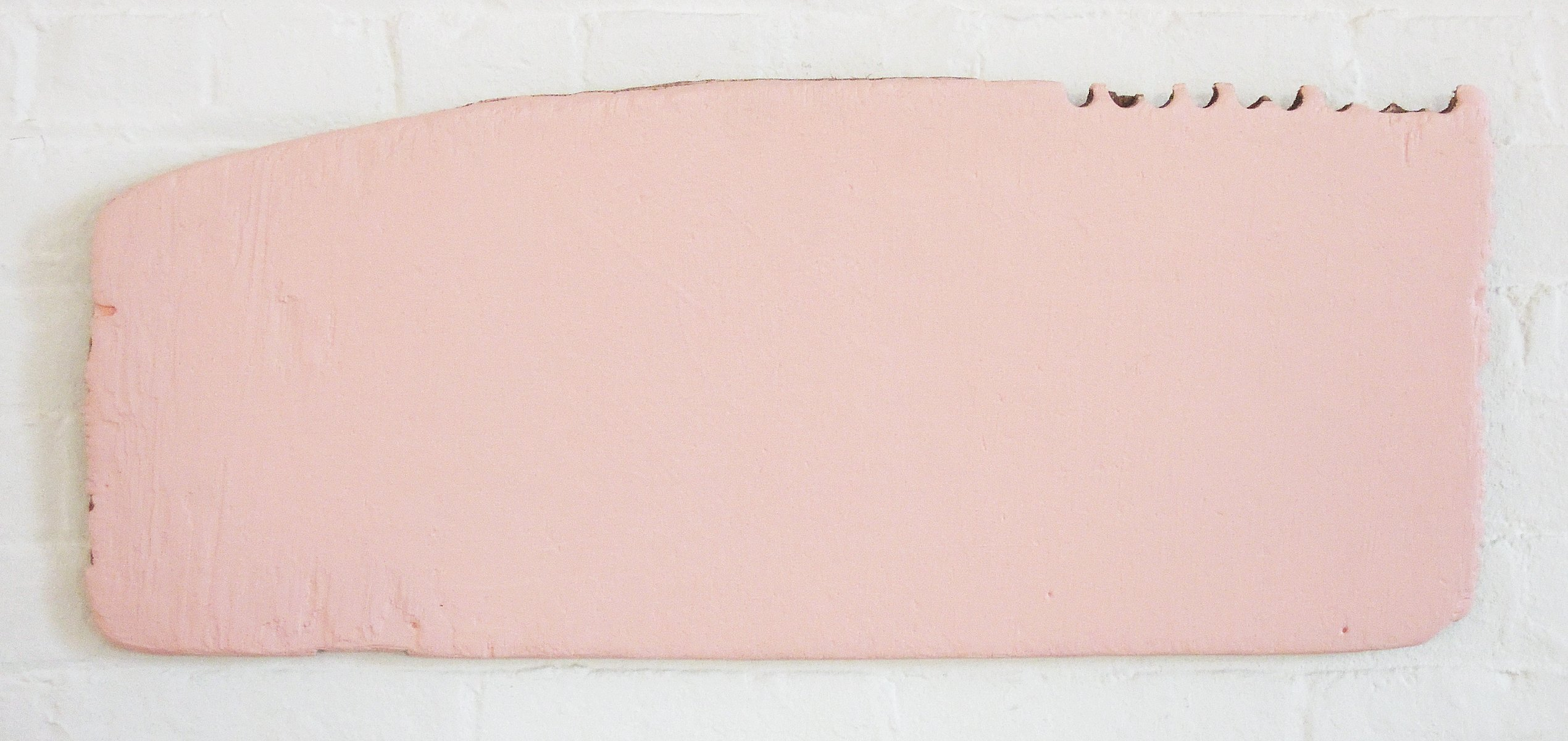 An irregularly shaped piece of plywood completely covered in pink paint.