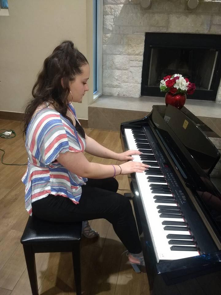 Girl sitting up-right and playing the piano