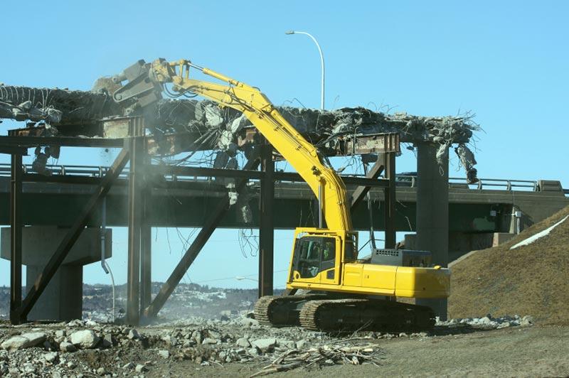 Excavator demolishing on highway overpass