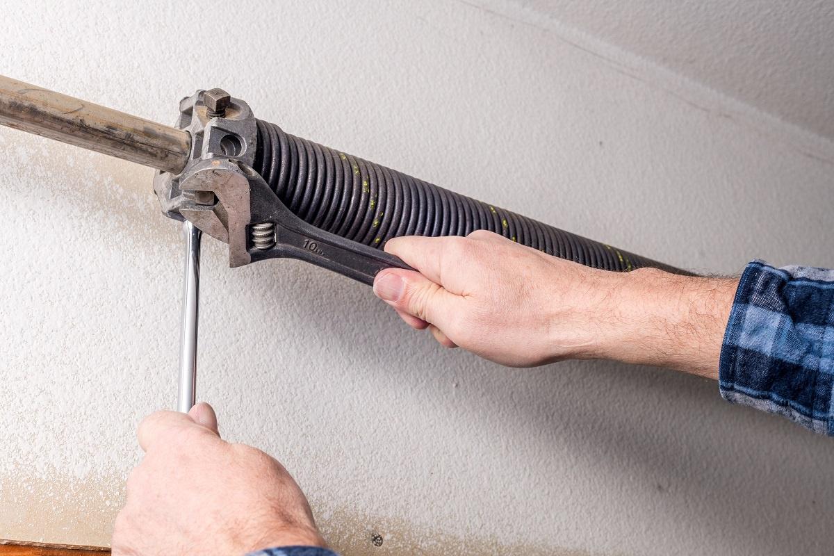Repairman Uses Tools to Work on a Garage Door Spring