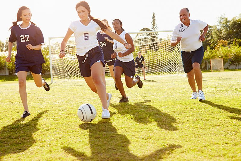 Female High School members playing soccer