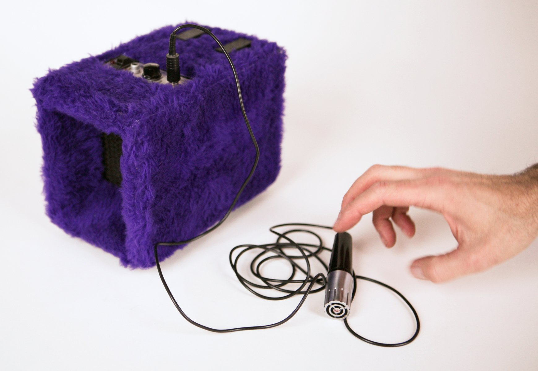 A hand reaches for a microphone plugged into a purple fur covered box device.