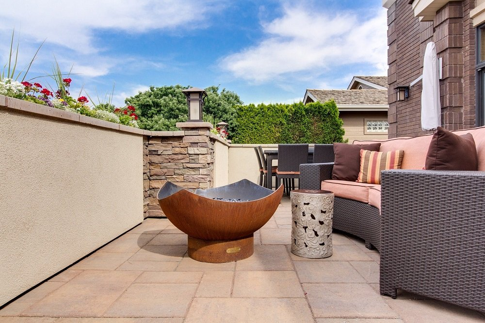 Paver Patio with Brown Modern Firepit and Gray and Orange Sofa