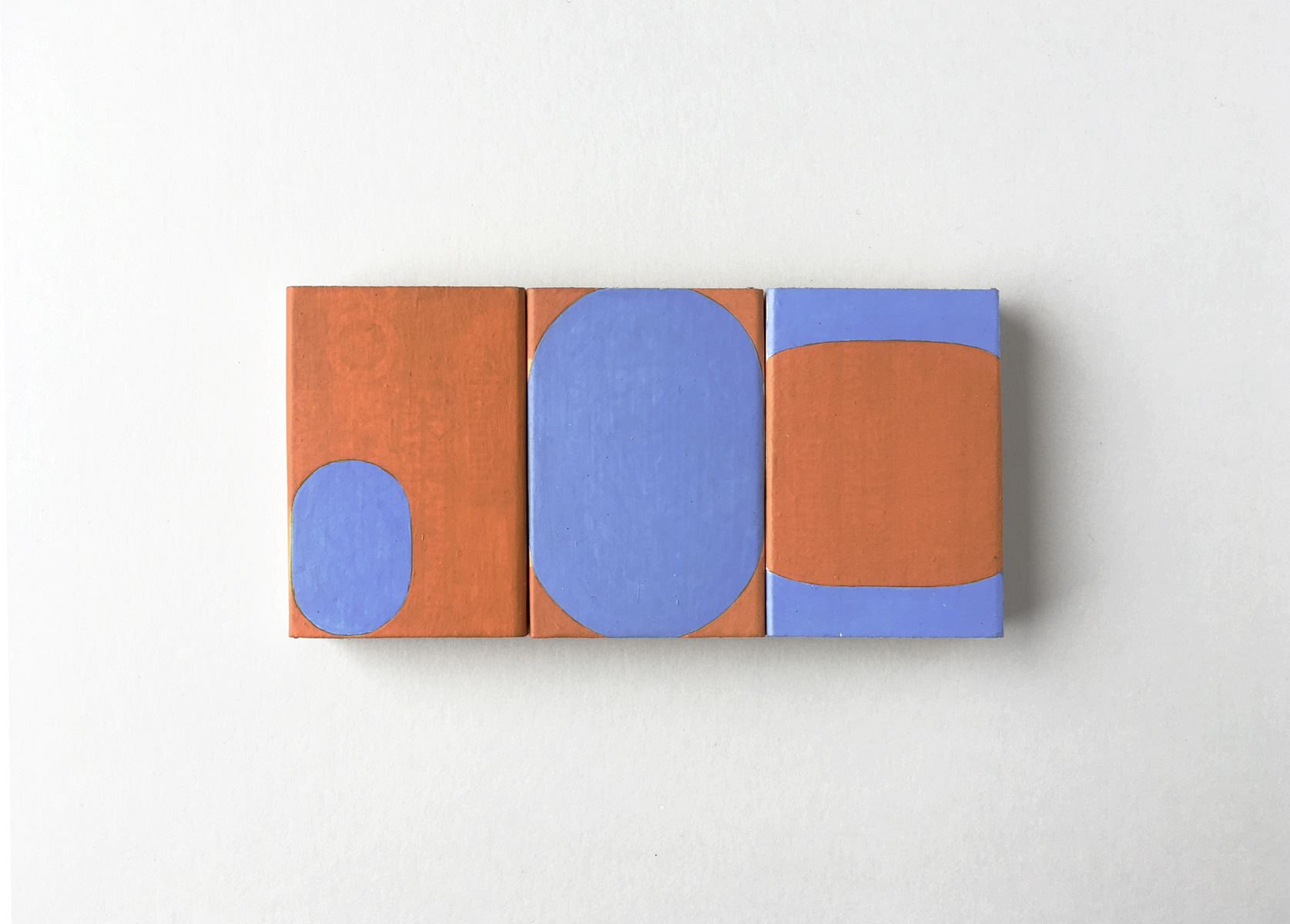 Three small matchboxes in a row with blue and orange ovals painted on them.