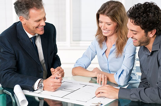 Real Estate Agent with Smiling Couple