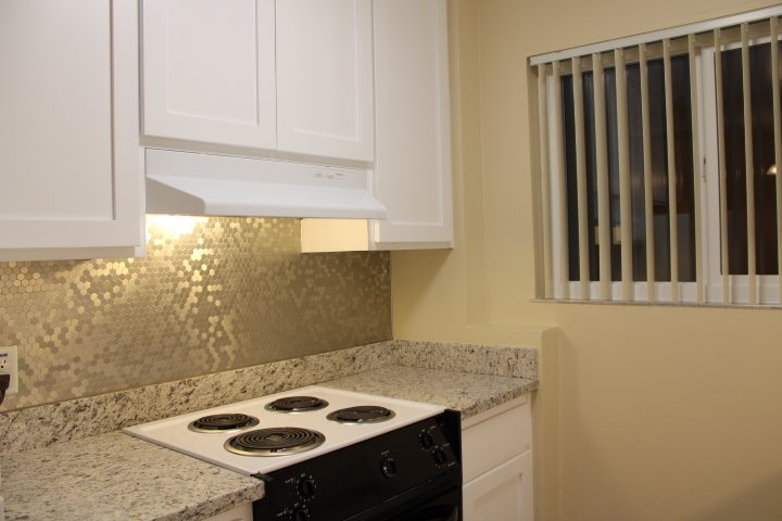 The kitchen has a new backsplash, new granite countertops, and new cabinets!