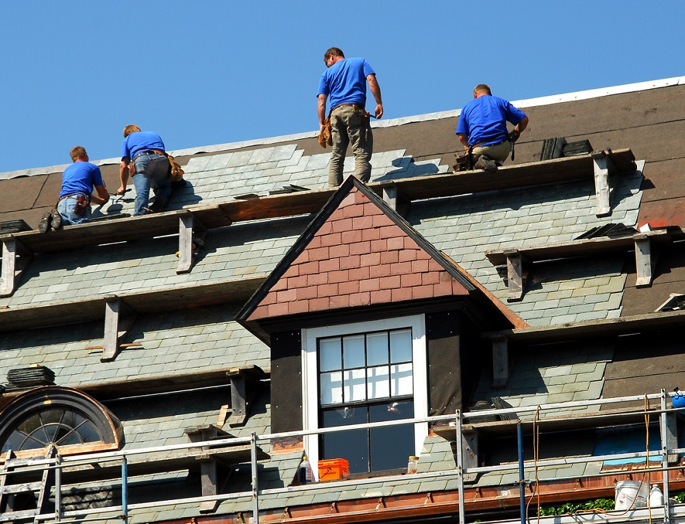 A group of roofing contractors installing shingles on the roof of a Dunwoody, Georgia residence