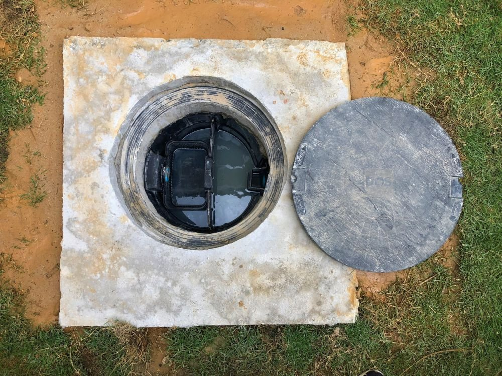 A hole of grease trap underground tank with the drain system around the house.