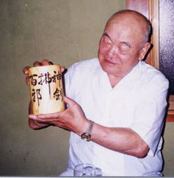 "1994. Nakamura Sensei shows a gift from Power Sensei.  The calligraphy-brush holder is engraved by an artisan with Araki Sadao Sensei's calligraphy ""Shin Ken Hyaku Ja Futsu""."