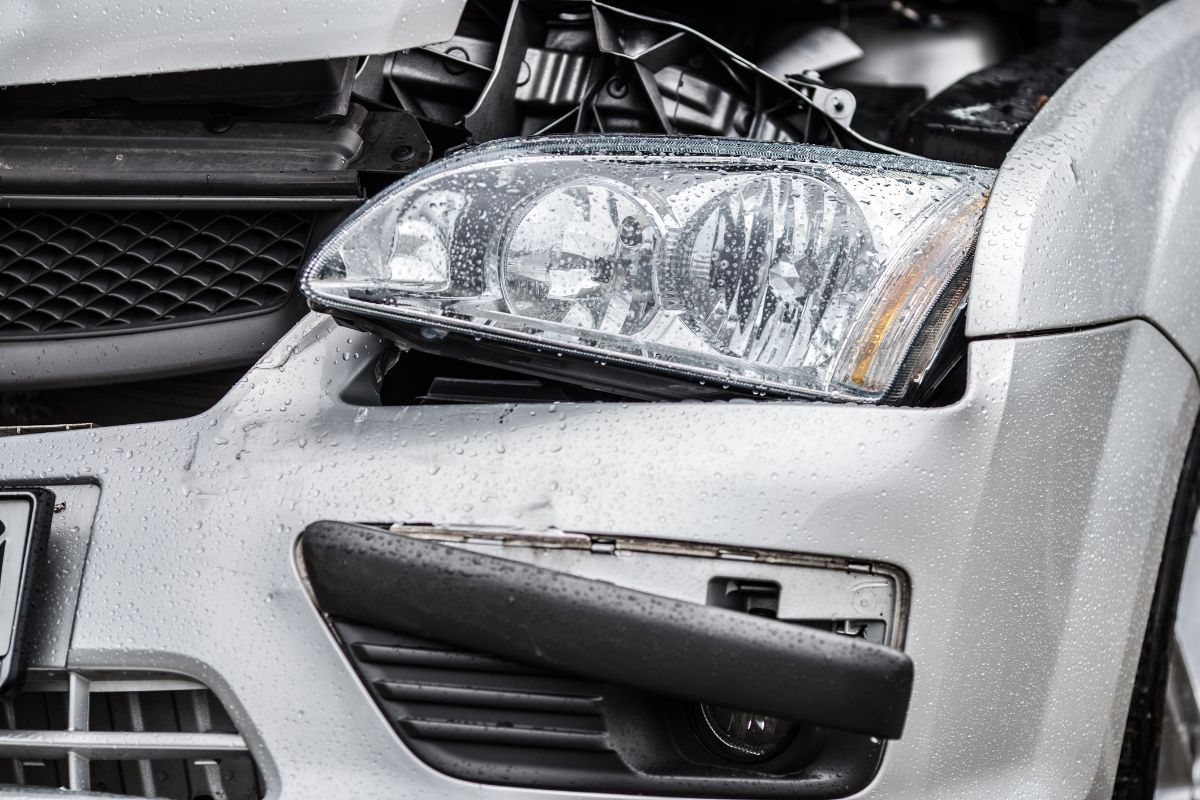 Damaged front / headlight of a silver car