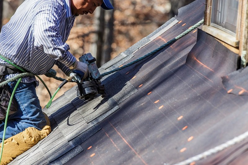 Roofer Uses Nail Gun to Secure Shingles
