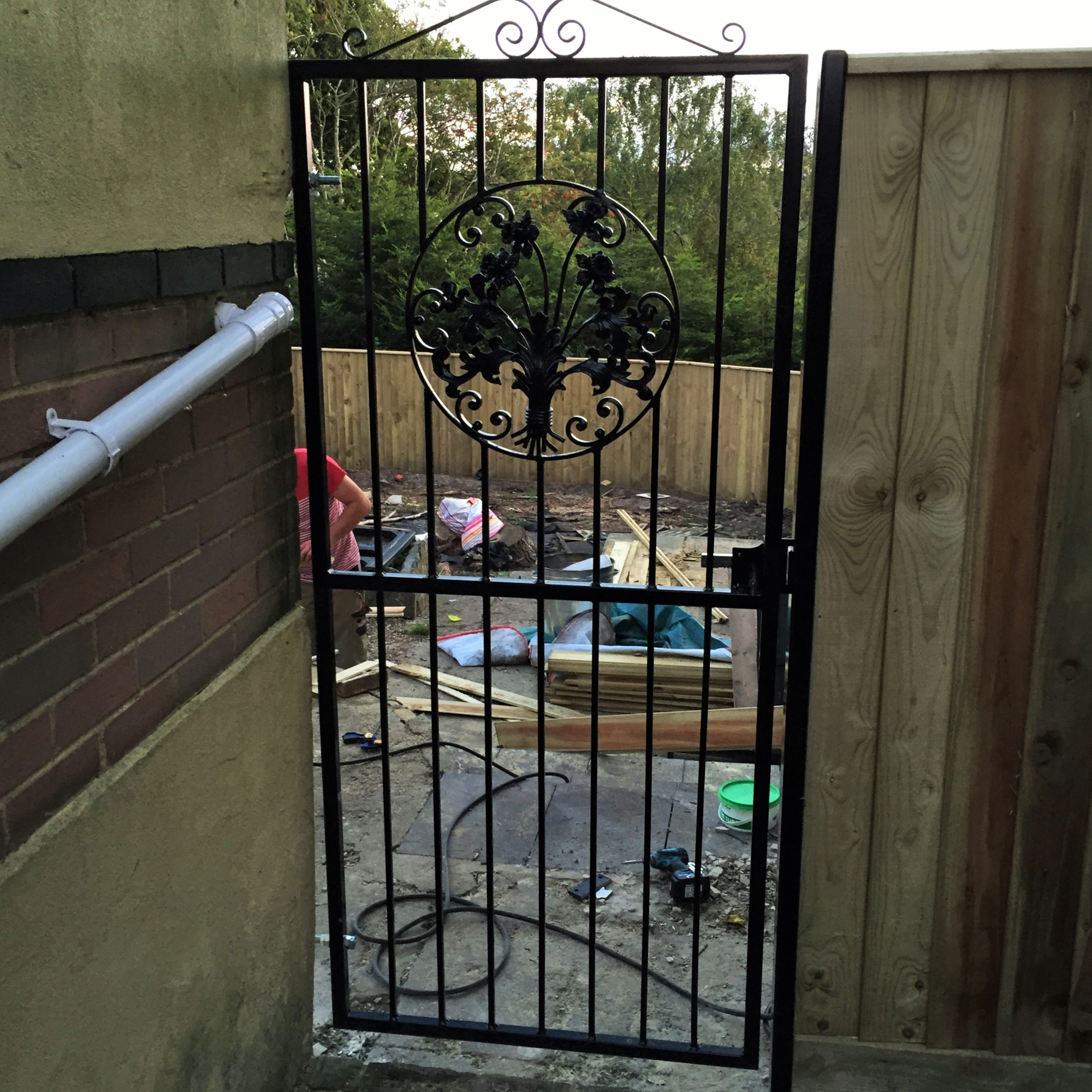 A single gate fabricated in our workshop powder coated in black (The building is out of square not the gate)