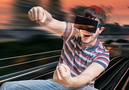 Happy young Man is Playing Racing Videogame in 3D Virtual Reality
