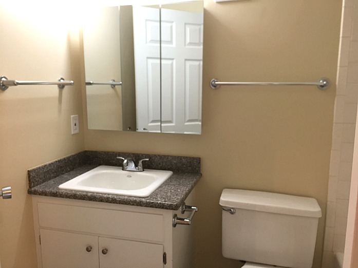 This bathroom also has a granite countertop and a large medicine cabinet