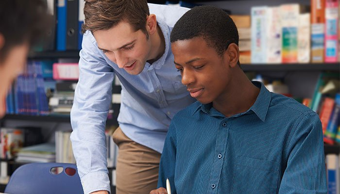 Teacher Helping Male Student In Classroom