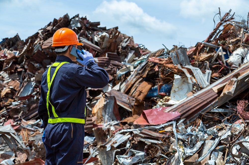 Worker in front of pile of scrap metal