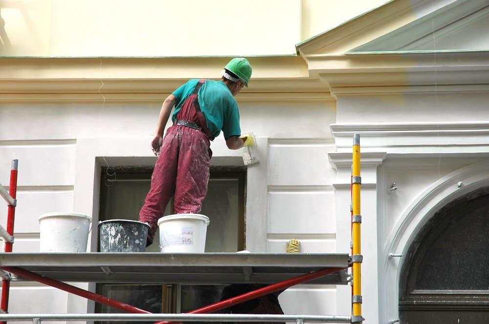 A professional house painter applying a flat sheen white paint to the exterior of a Phoenix, Arizona area home