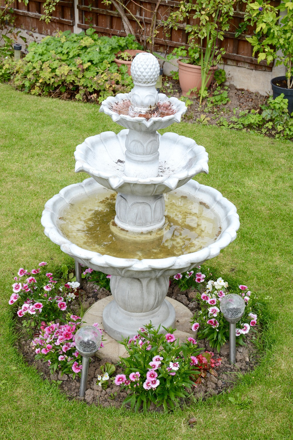 Small 3 tier water fountain with flowers around base