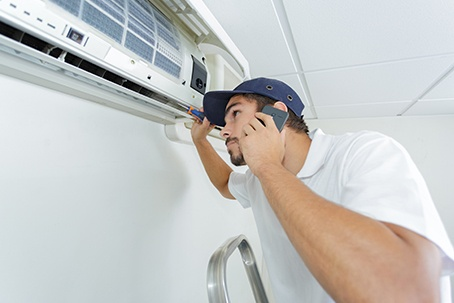Handyman Repairing Air Conditioning