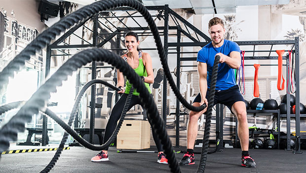 Woman And Man In The Gym With Battle Rope