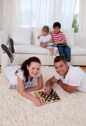 Couple playing chess on floor in living room