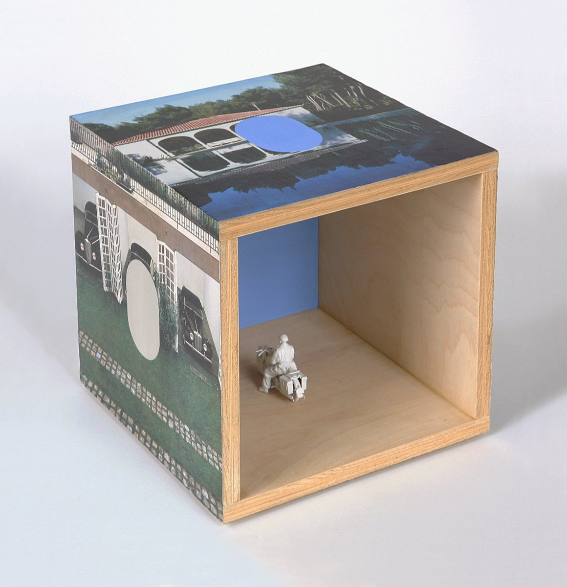 A plywood cube with imagery on the outside and a motorcycle model inside.