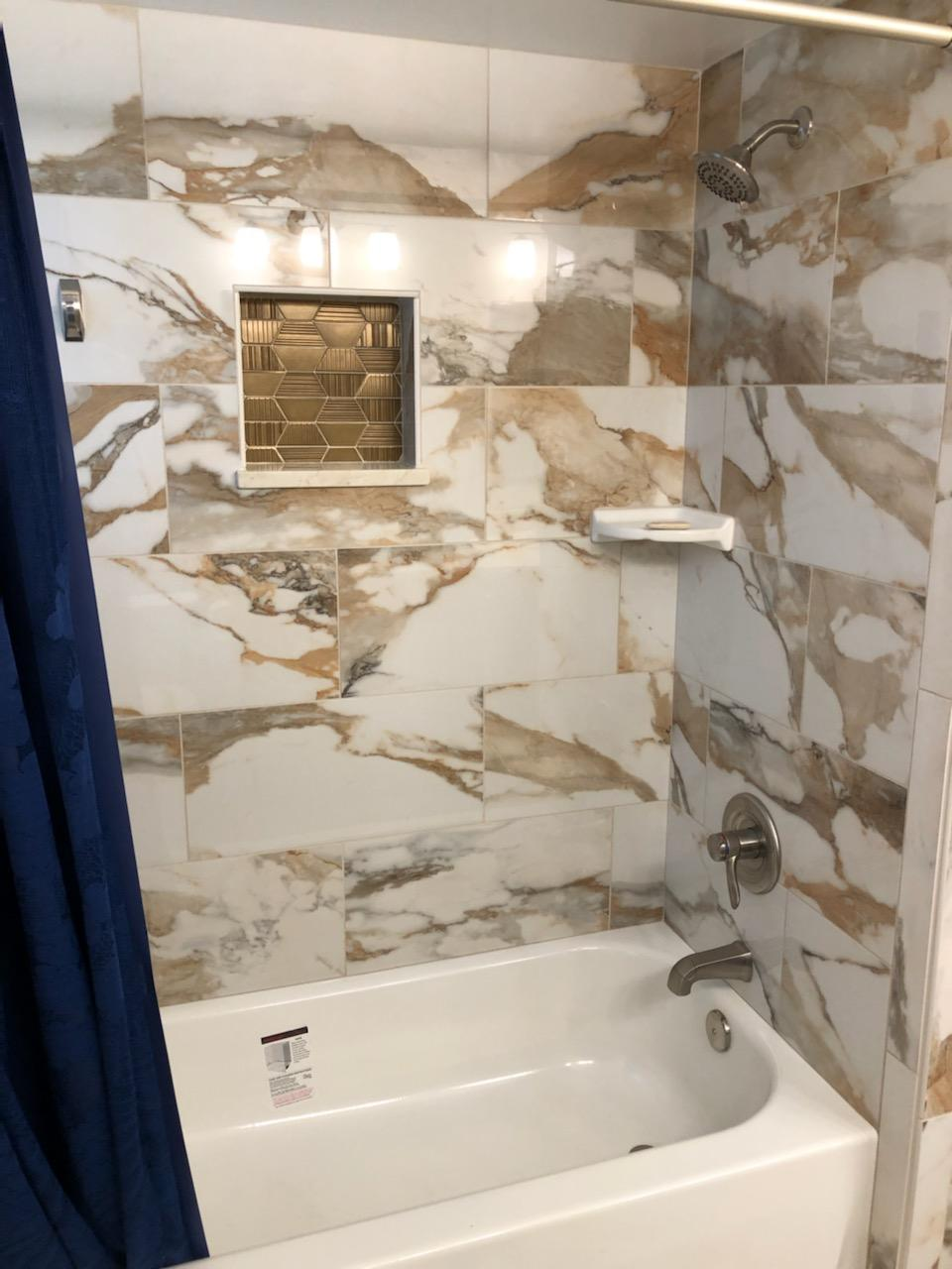 Dazzling shower tub combo with decorative gold mosaic niche.