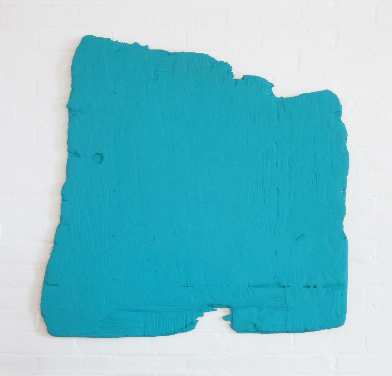 An irregularly shaped piece of plywood completely covered in turquoise paint.