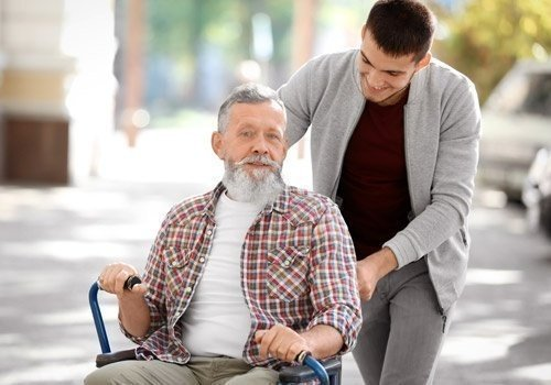 Young Caregiver Walking With Senior Man